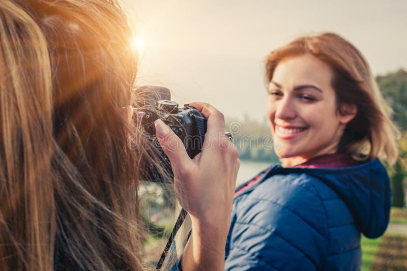 Tirado de un fotógrafo de la muchacha que toma una foto de un su amigo imagenes de archivo