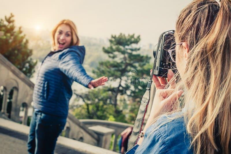 Tirado de un fotógrafo de la muchacha que toma una foto de un su amigo imagen de archivo
