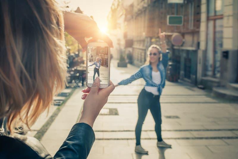 Tirado de un fotógrafo de la muchacha que toma una foto de un su amigo imagen de archivo libre de regalías