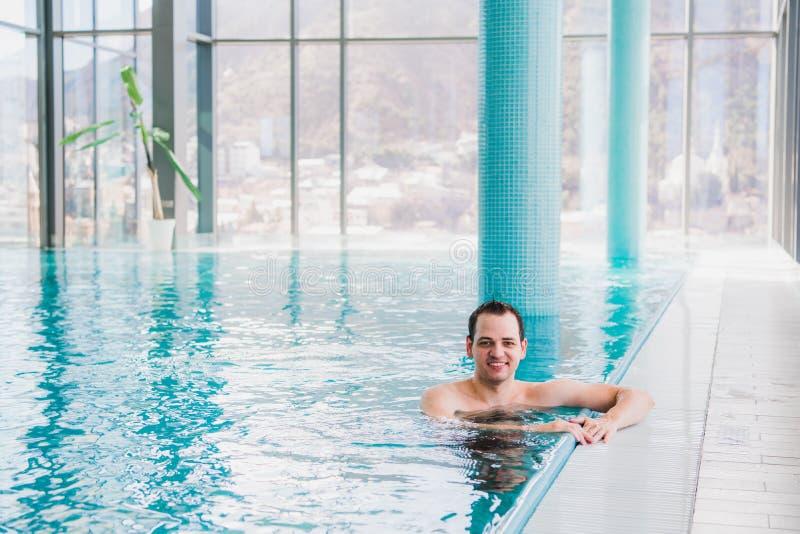 Tirado de un hombre feliz joven hermoso en la piscina interior imagenes de archivo