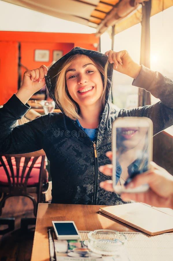 Tirado de una muchacha que toma una foto de un su amigo con el teléfono móvil imagen de archivo