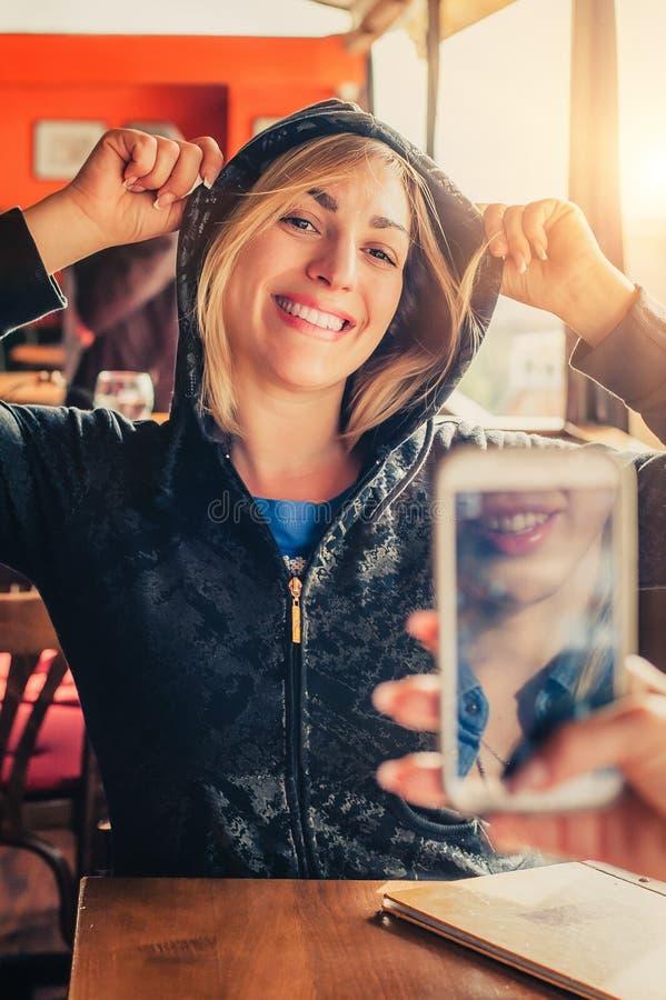 Tirado de una muchacha que toma una foto de un su amigo con el teléfono móvil foto de archivo