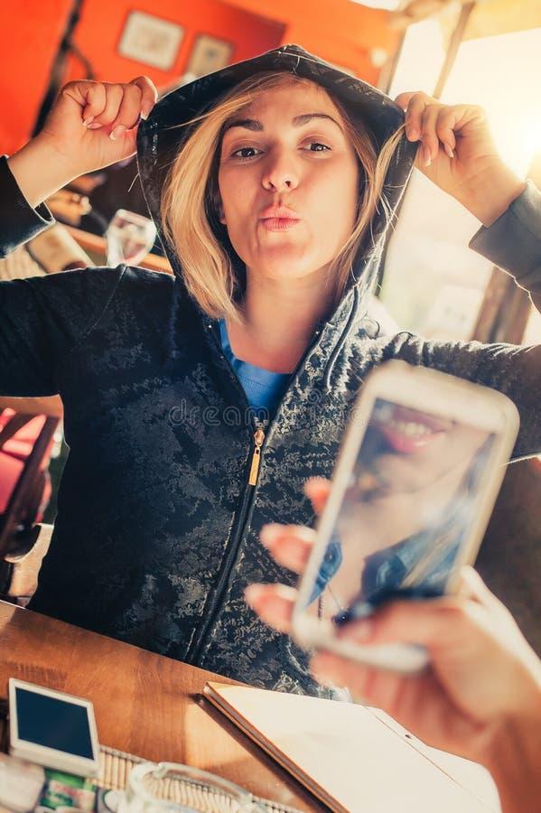 Tirado de una muchacha que toma una foto de un su amigo con el teléfono móvil fotos de archivo libres de regalías