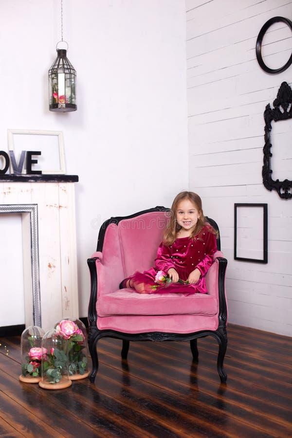 Tirado de una niña hermosa en un vestido con una rosa en sus manos que miran la cámara con una sonrisa encantadora que se sienta  imagen de archivo