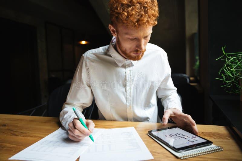 Tirado del freelancer joven del readhead serio que trabaja en el café fotografía de archivo libre de regalías