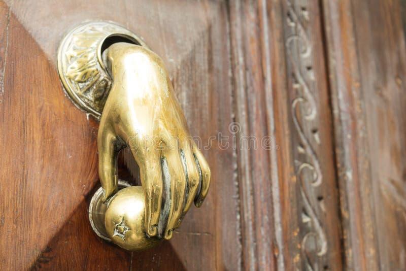 Tirador con la forma una mano en una puerta de madera vieja fotografía de archivo