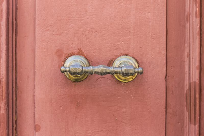 Tirador de puerta aherrumbrado de una puerta de madera roja fotografía de archivo