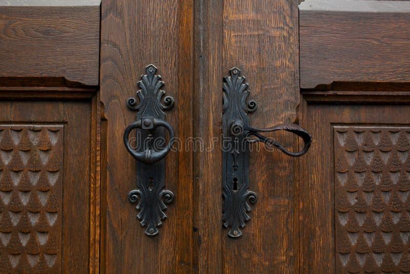 Tirador de puerta hecho a mano del hierro en puerta de madera decorativa marrón foto de archivo libre de regalías