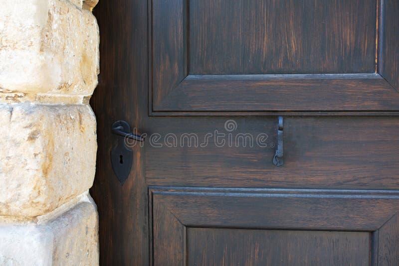 Tirador de puerta negro del vintage de una puerta de madera marrón fotografía de archivo