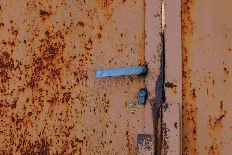 Tirador gris en una pared oxidada marrón vieja imagen de archivo libre de regalías