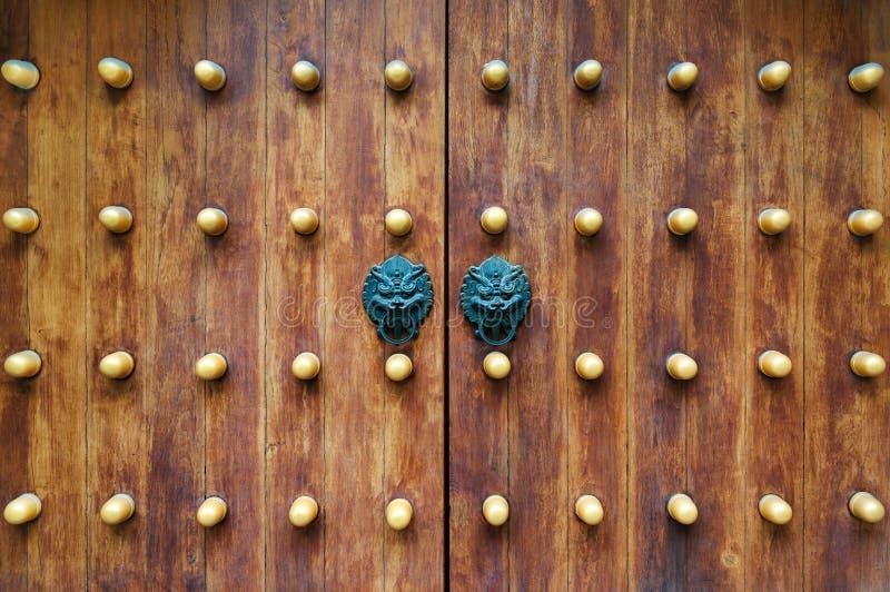 Tirador tradicional chino y puertas de madera Manija vieja del metal en una puerta vieja de madera Golpeador de puerta en la form fotografía de archivo libre de regalías