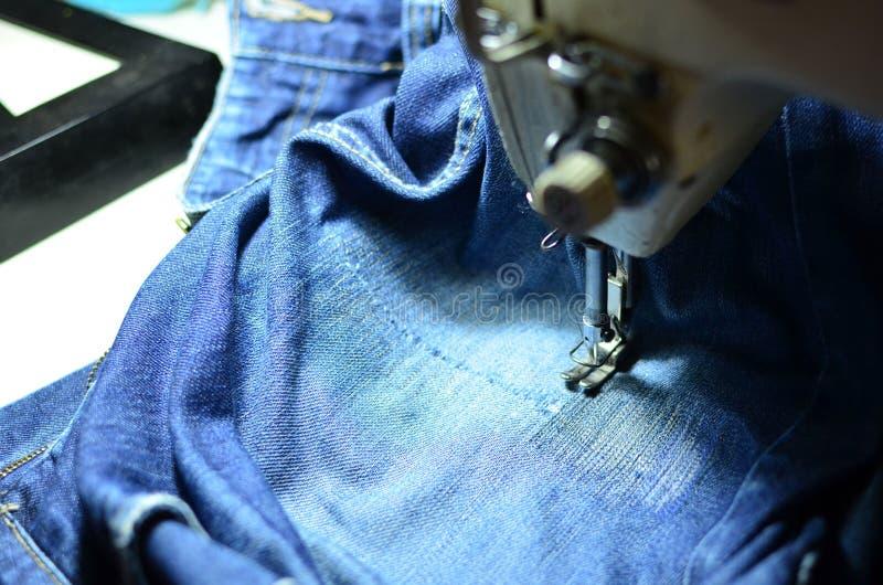 Tirage, couture d'un trou dans un jean bleu avec une machine à coudre Partie de la machine à coudre et du tissu de jeans photo stock