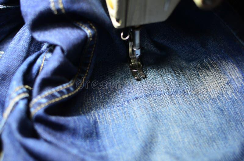 Tirage, couture d'un trou dans un jean bleu avec une machine à coudre Partie de la machine à coudre et du tissu de jeans photographie stock
