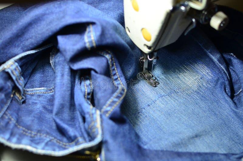 Tirage, couture d'un trou dans un jean bleu avec une machine à coudre Partie de la machine à coudre et du tissu de jeans photo libre de droits
