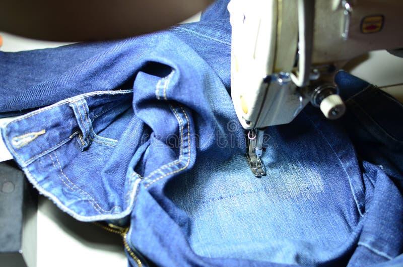 Tirage, couture d'un trou dans un jean bleu avec une machine à coudre Partie de la machine à coudre et du tissu de jeans photos stock