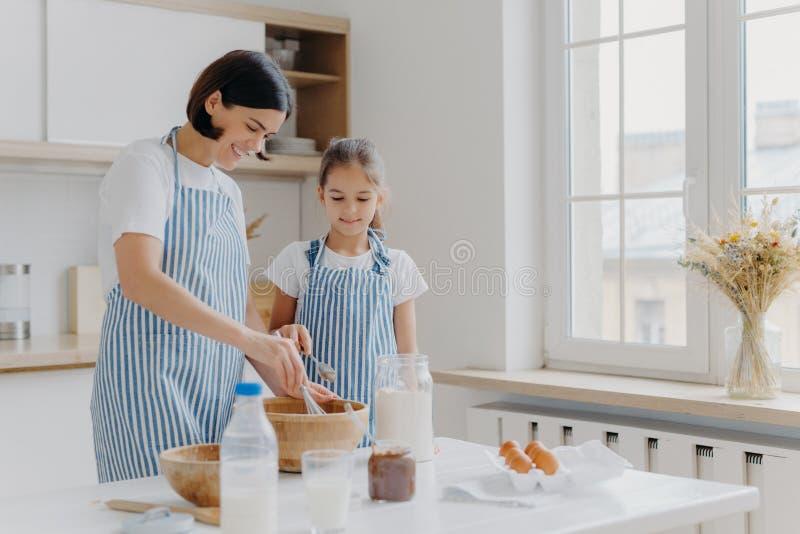 Tirage horizontal de la mère et de la fille qui s'occupent de cuisiner ensemble, la mère donne une leçon culinaire à la petite fi photos libres de droits