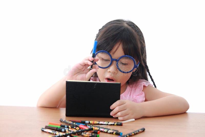 Tiraggio asiatico della bambina su un libro fotografia stock libera da diritti