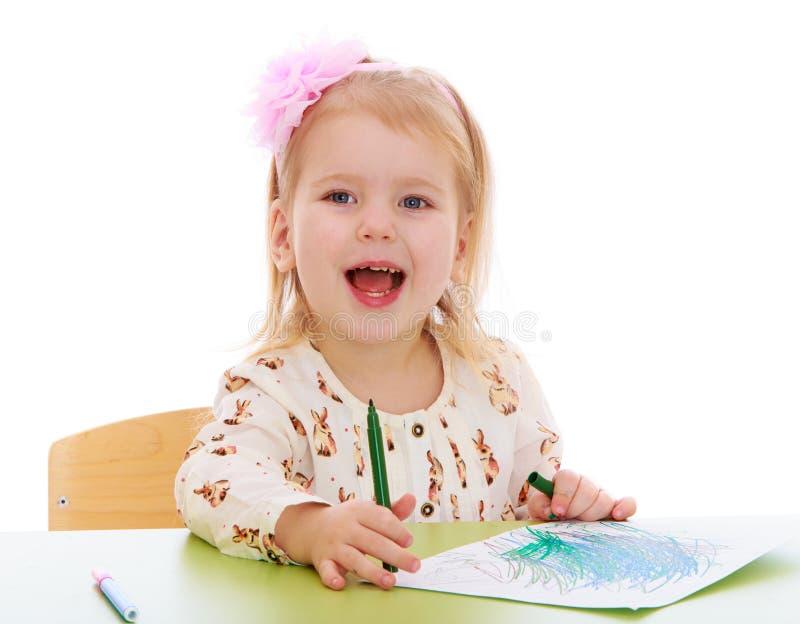 Tiraggio biondo della bambina con seduta del pennarello fotografia stock libera da diritti