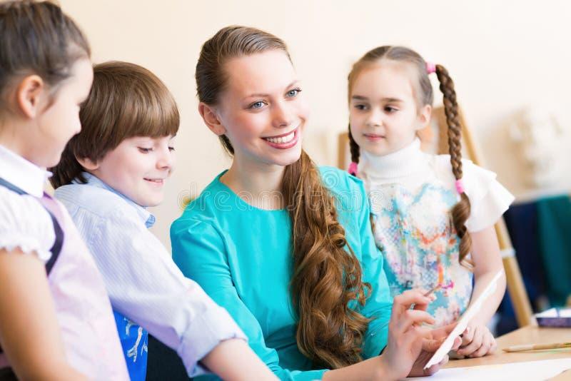 Tiraggio dei bambini con l'insegnante immagini stock