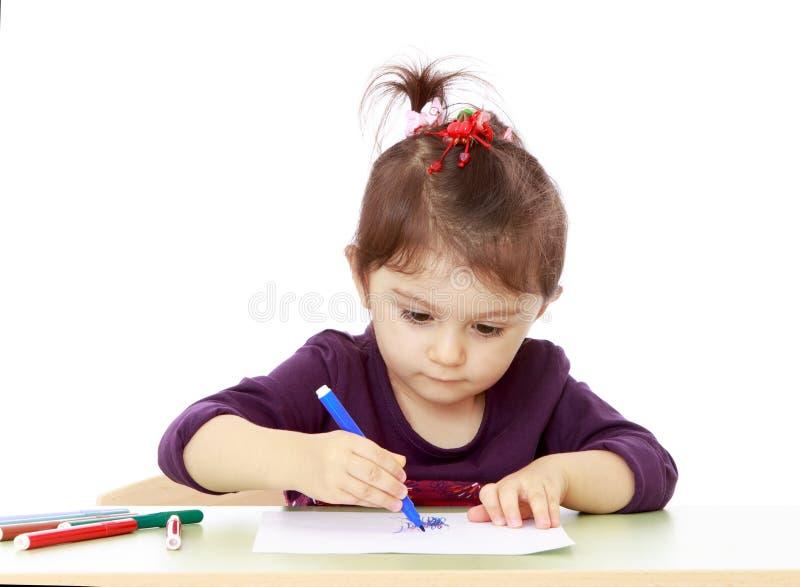Tiraggio entusiasta della bambina con il pennarello che si siede a fotografia stock