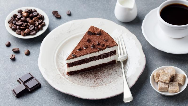 Tiramisu cake with chocolate decotaion on a plate with cup of coffee. Grey stone background. stock image
