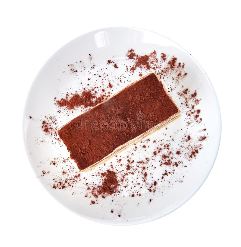 Tiramisu cake/ dessert with cacao on a porcelain plate on the white background royalty free stock photo