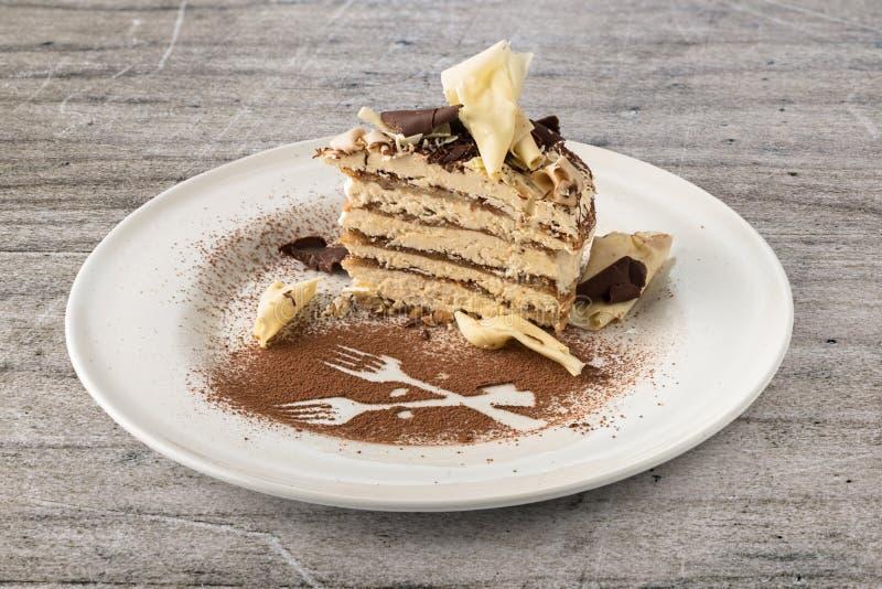 Tiramisu cake with white and dark chocolate flakes. On a plate stock image