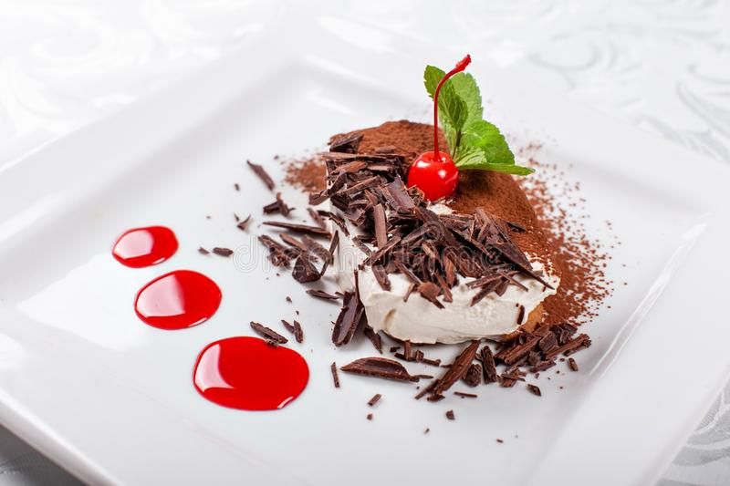 Tiramisu. Classical Dessert with cocoa and chocolate on white square plate. Garnished with Cherry and Mint. Sweet royalty free stock image