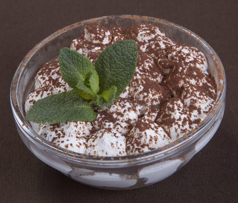 Tiramisu de dessert avec du chocolat et les feuilles en bon état sous une forme en verre ronde photos libres de droits