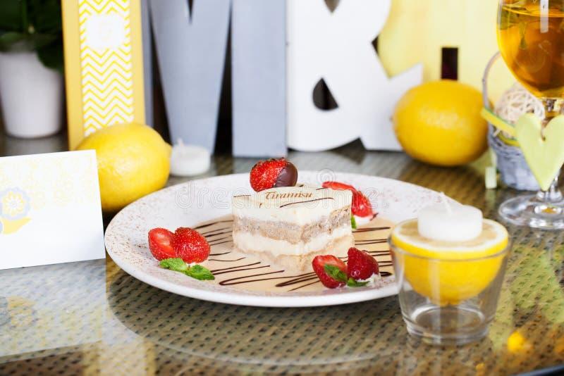 Tiramisu med jordgubbar på en plattacitronbokstav royaltyfri fotografi