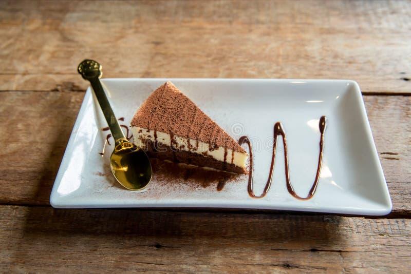 Tiramisu na biel talerzu Wy?mienicie Tiramisu tort z kawowymi fasolami i ?wie?? mennic? na talerzu na lekkim tle obrazy royalty free