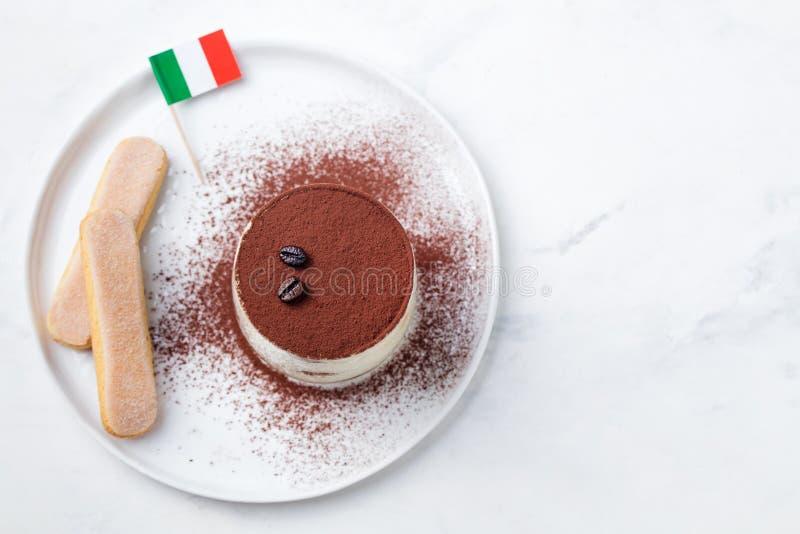 Tiramisu, postre italiano tradicional en una placa blanca con el espacio italiano de la copia de la opinión superior de la bander fotografía de archivo libre de regalías