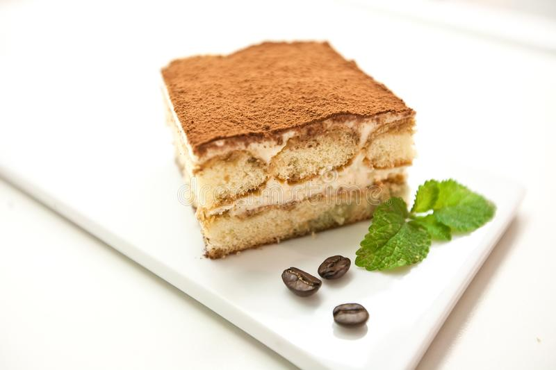Tiramisu, traditional Italian dessert on a white plate. Close up. royalty free stock photo