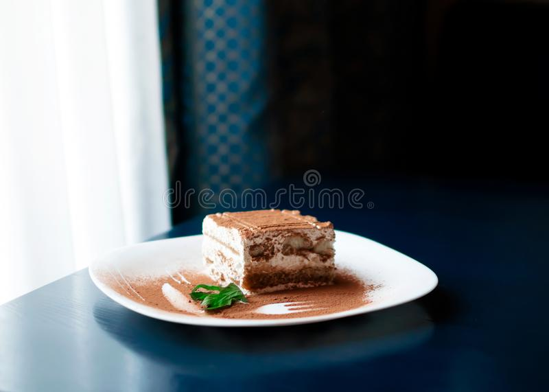 Tiramisu traditional Italian dessert on white plate on dark blue table next to roon window with curtains . Withe day light from th. E window. Close up food with stock photo