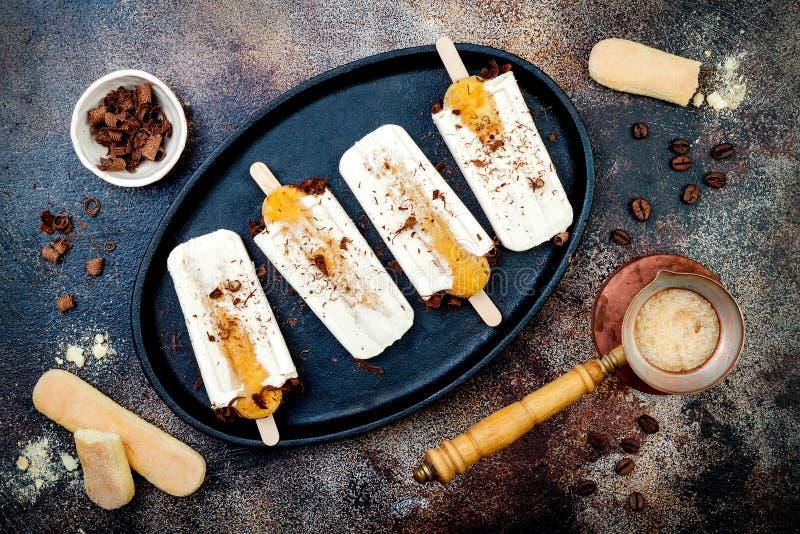 Tiramisueis am stiel Wassereise mit italienischen savoiardi Plätzchen und Tiramisubestandteilen auf rustikalem Küchentisch lizenzfreie stockbilder