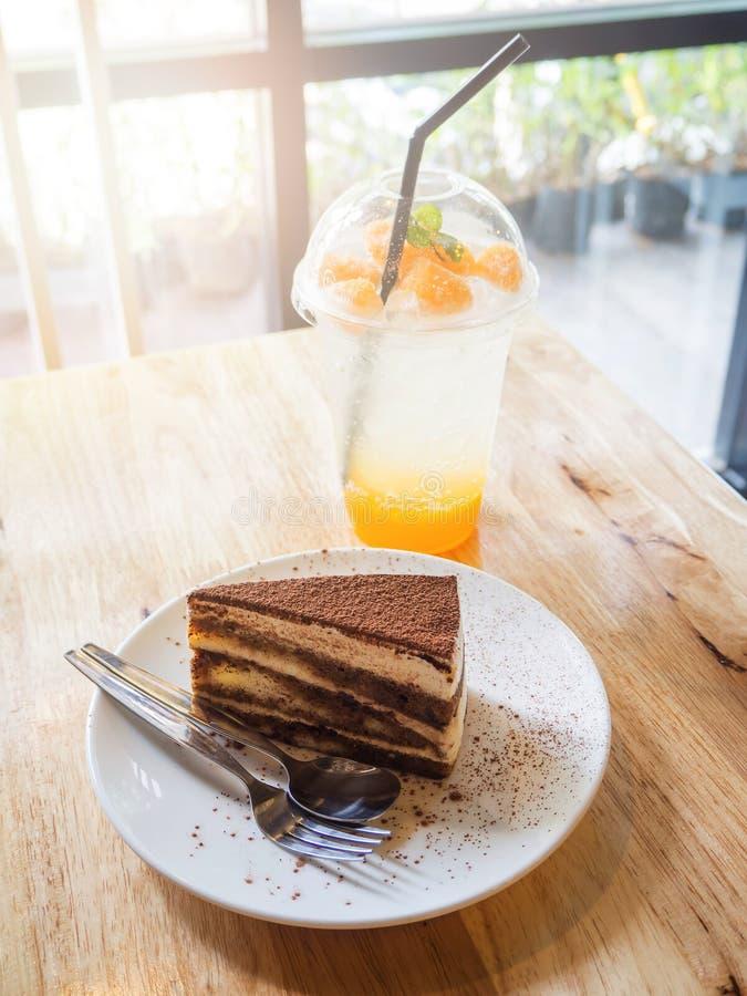 Tiramisukaka och exponeringsglas av orange sodavatten på trätabellen royaltyfria bilder