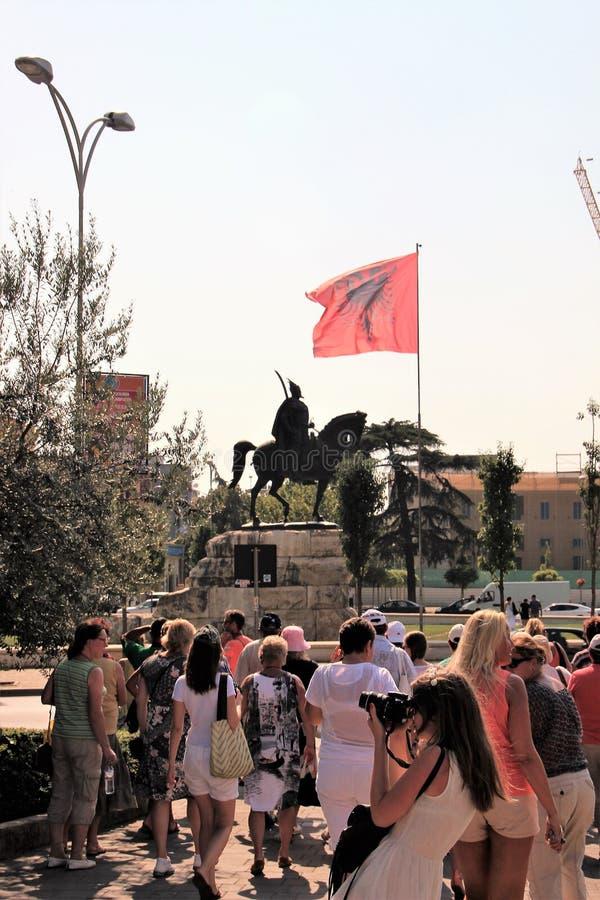 Tirana, Albanië, Augustus 2013 Een groep toeristen voor het monument aan de nationale held royalty-vrije stock fotografie