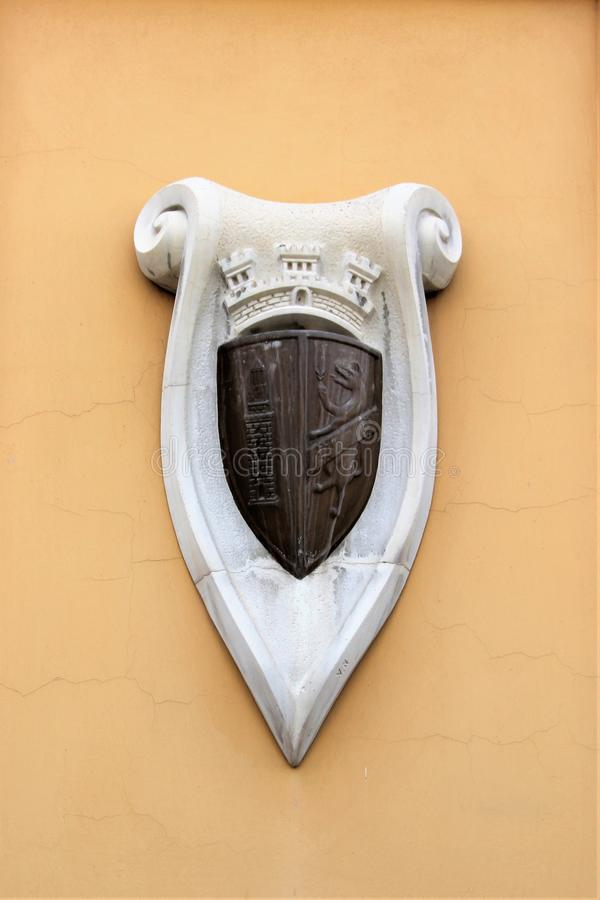 Tirana, Albania, August 2013. The emblem of the capital on the stone wall of the building. Excellent medieval heraldic shield with the symbols of the city, the stock images