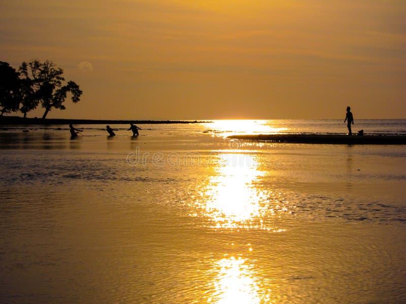 Tirando en los días coja, familia de pescadores que trabajan junto en la puesta del sol foto de archivo