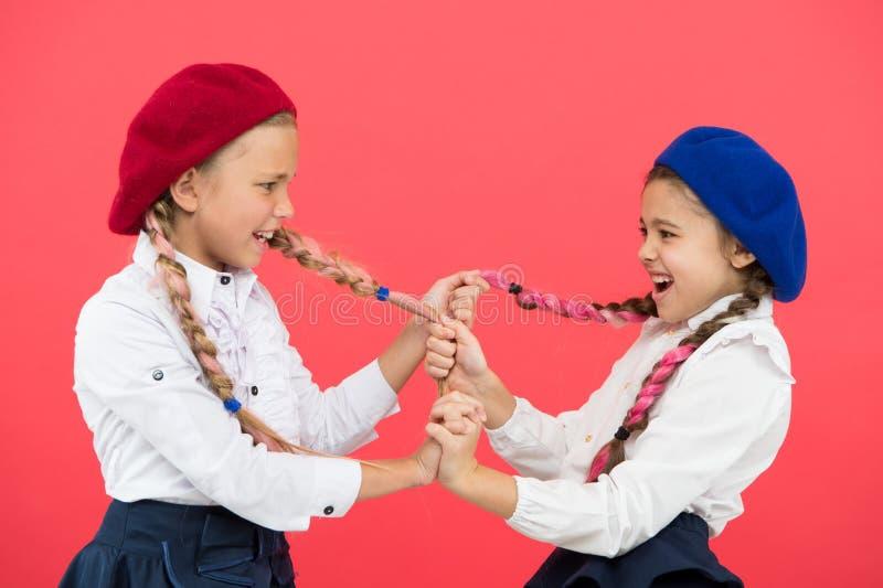 Tiranizar e agressão Crianças impertinentes que puxam as tranças no fundo cor-de-rosa Meninas pequenas com comportamento tiraniza foto de stock