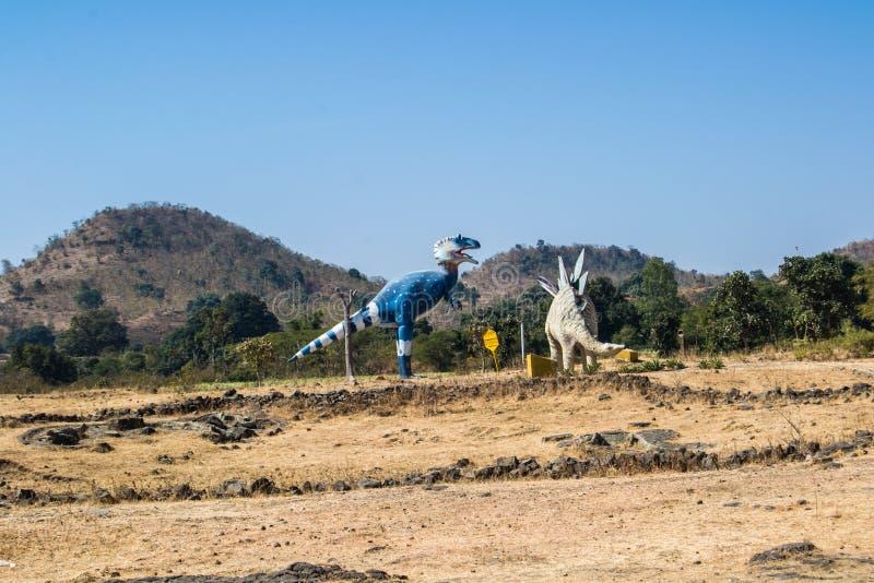 Tiranossauro do dinossauro e escultura ou efígie do Stegosaurus na floresta fotos de stock royalty free