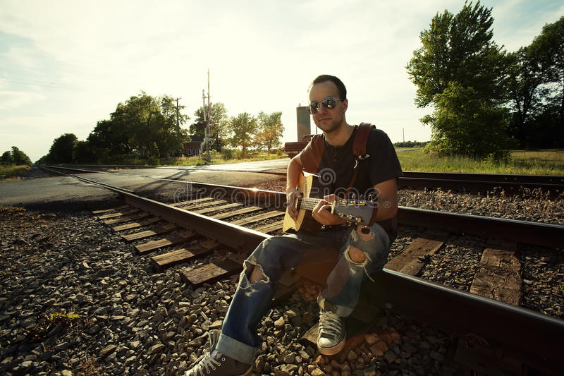 Tirante che si siede sulle rotaie con la chitarra immagini stock libere da diritti