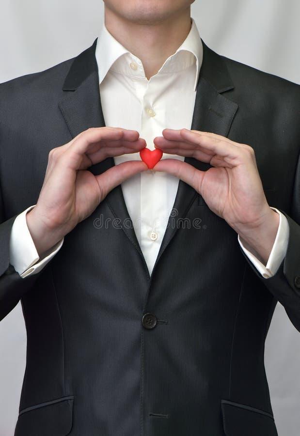Tirante che tiene un cuore rosso fotografie stock