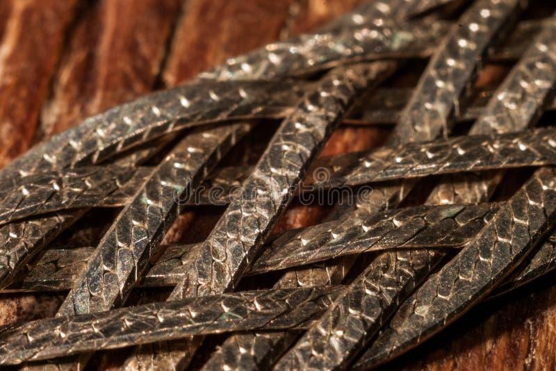 Tiras de metal trançadas com escalas fotografia de stock royalty free