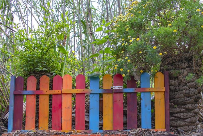 Tiras y wicketes multicolores de la cerca en la entrada a un jardín demasiado grande para su edad imágenes de archivo libres de regalías