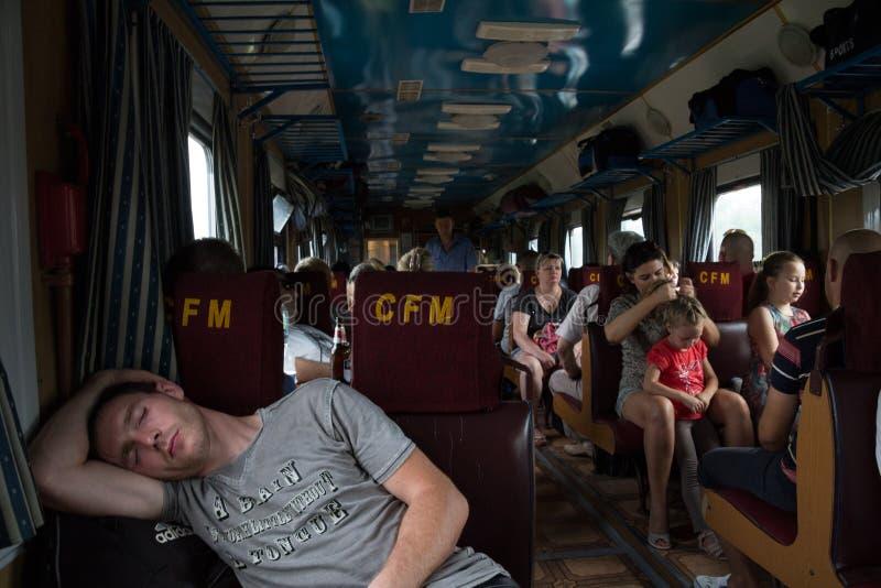 TIRASPOL, TRANSNITRIA MOLDAVIA - 13 AGOSTO 2016: Giovane che dorme in una carrozza ferroviaria di Chisinau-Odessa immagine stock