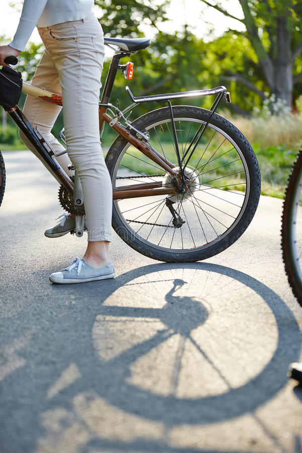 Tire of bike on a road. With legs of a woman stock photography