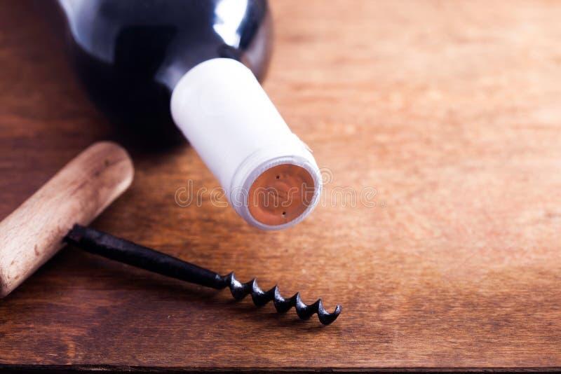 Tire-bouchon de vintage et bouteille de vin sur le conseil photographie stock