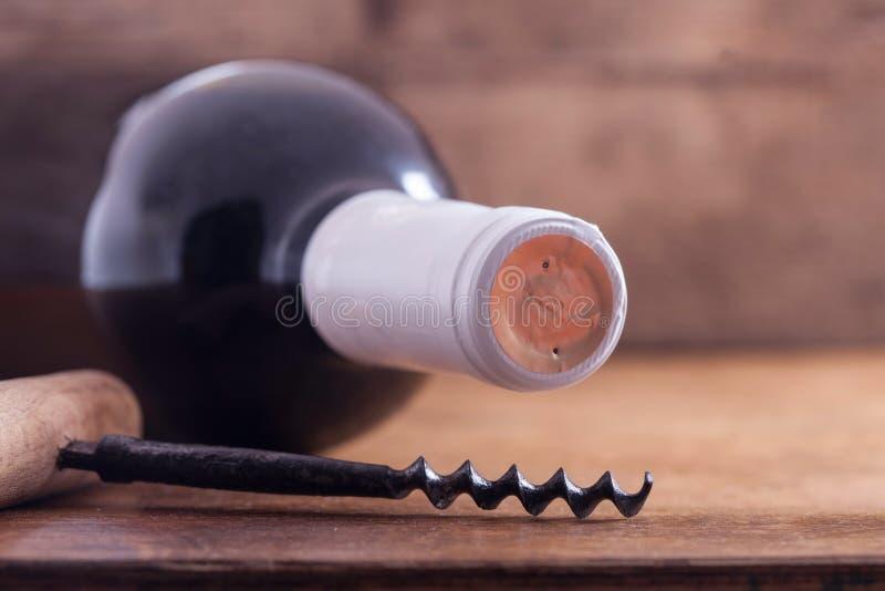 Tire-bouchon et bouteille de vin sur le conseil photographie stock