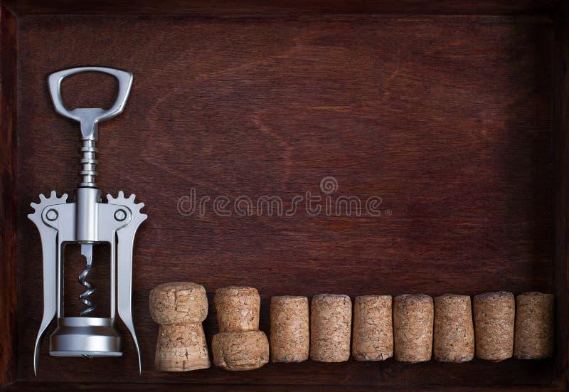 Tire-bouchon et rangée des lièges de vin dans la boîte foncée image libre de droits
